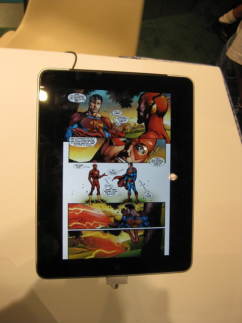 An iPad showing a page of a comic book with Superman and the Flash in it.